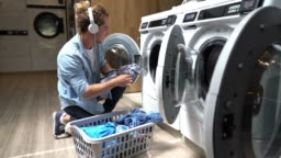 Happy young man at a laundromat loading washing machine while listening music