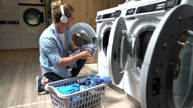 happy young man at a laundromat loading washing machine while listening music - laundry stock videos & royalty-free footage