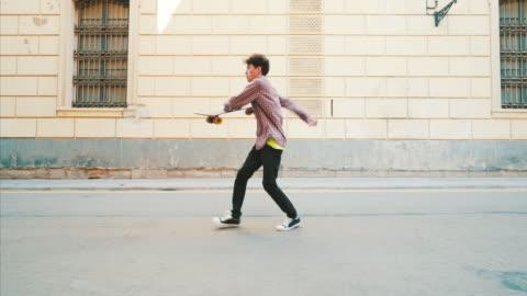 glücklicher junger mann tanzt auf der straße. - one person stock-videos und b-roll-filmmaterial
