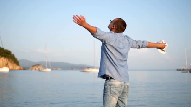 glücklicher junger mann am strand - turning stock-videos und b-roll-filmmaterial