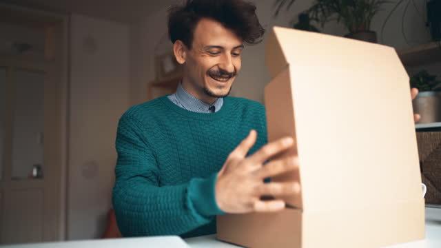 vídeos y material grabado en eventos de stock de feliz joven abriendo paquete de entrega en casa - regalo