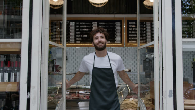 happy young man opening for service at the butcher's shops looking away daydreaming - new business stock videos & royalty-free footage