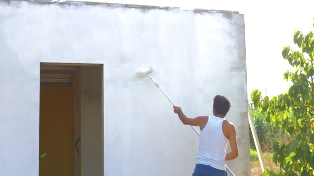happy young man painting his house in white while dances - 白しっくい塗点の映像素材/bロール