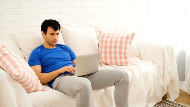 Glücklicher junger Mann auf Sofa sitzen und arbeiten mit Laptop-Computer zu Hause