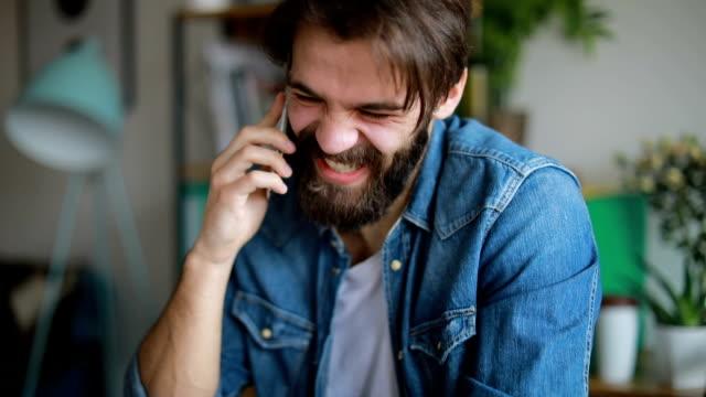 Glücklich Jüngling am Telefon zu sprechen und auf seinem Laptop arbeiten