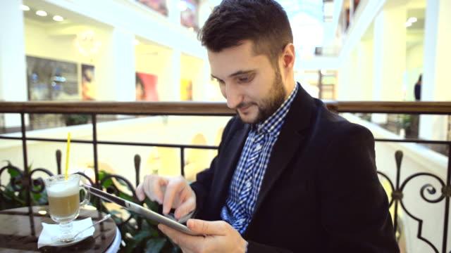 vídeos y material grabado en eventos de stock de feliz joven con tableta en el centro comercial. - barba de tres días