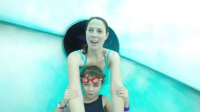 Happy young mother and child girl enjoying water slide