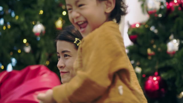 happy young mother having fun with her kids in christmas time next to christmas tree - ornato video stock e b–roll