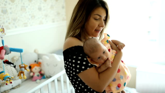 happy young mother holding and singing to her newborn baby - baby clothing stock videos & royalty-free footage