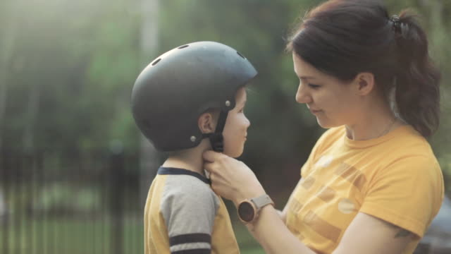 happy young mother is putting a bicycle safety helmet on her little son's head. - helmet stock videos & royalty-free footage