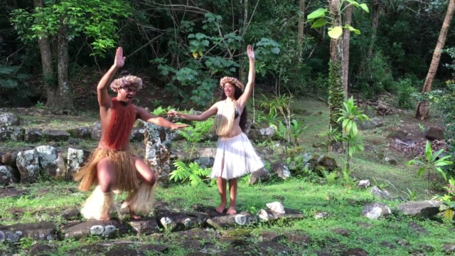 vídeos de stock e filmes b-roll de happy young pacific islander couple dancing in a ancient maori marae in the highlands of rarotonga cook islands - cultura polinésia