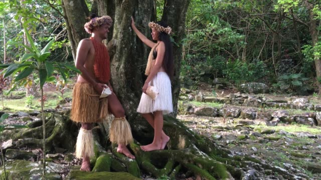 Happy young Pacific Islander couple in a ancient Maori Marae in the highlands of Rarotonga, Cook Islands