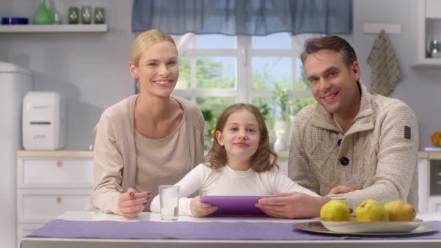 glückliche junge eltern spielt mit tochter, einsatz neuer technologien im wohnzimmer - junge familie stock-videos und b-roll-filmmaterial