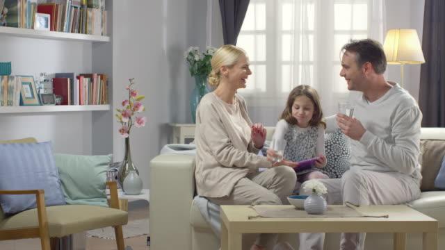 Glückliche junge Eltern spielt mit Tochter, die mit neuen Technologien im Wohnzimmer