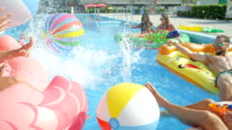 SLOW MOTION: Happy young people having fun splashing water on colorful floaties