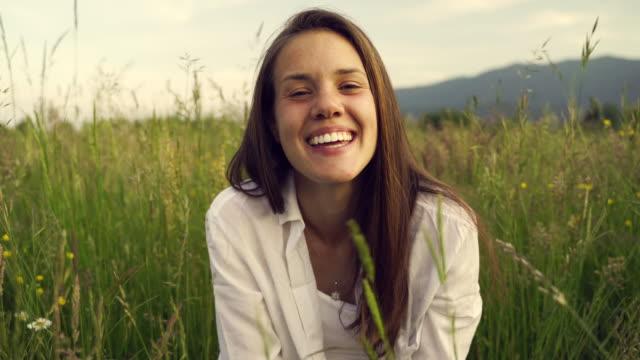 vidéos et rushes de jeune femme heureuse soufflant des têtes de fleur vers l'appareil-photo sur le pré - sitting