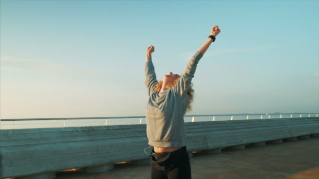 vídeos y material grabado en eventos de stock de feliz joven celebrando sus resultados de entrenamiento. - ganar