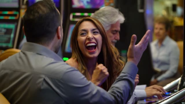 happy young woman celebrating with the man next to him a win on the slot machines - casinò video stock e b–roll