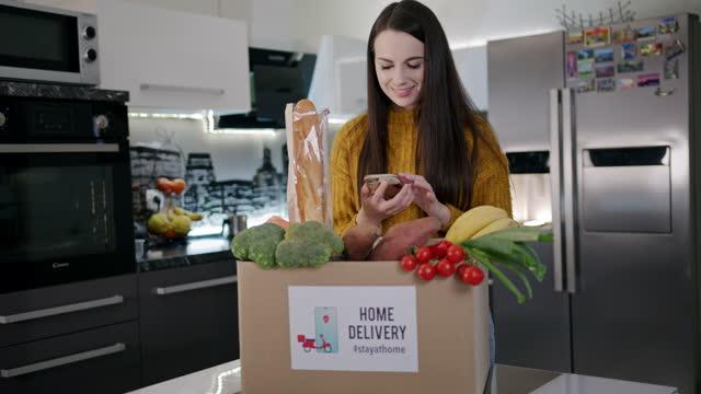 vidéos et rushes de slow motion jeune femme heureuse confirmant la livraison de boîte de nourriture - produit bio