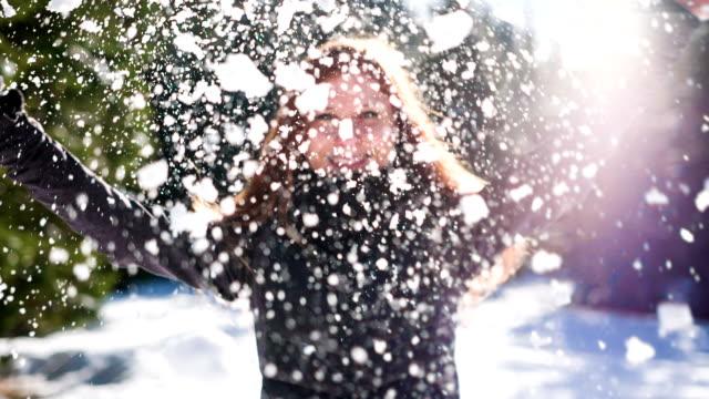 vídeos y material grabado en eventos de stock de mujer joven feliz aplastar una bola de nieve en el aire - nieve en polvo