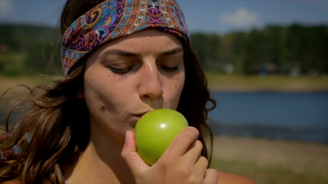 vídeos de stock e filmes b-roll de happy young woman eating an apple - hippie