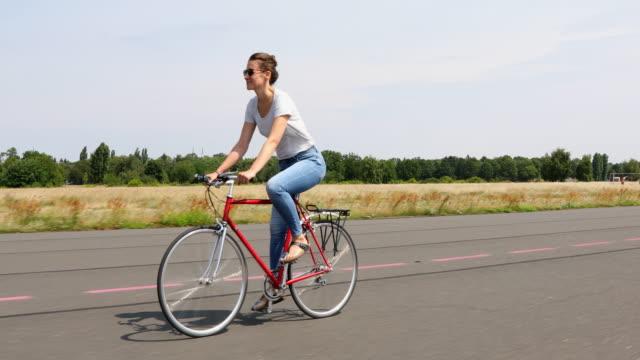 glückliche junge frau genießen die freiheit von radfahren - cycling stock-videos und b-roll-filmmaterial