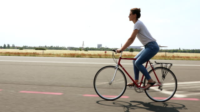 happy young woman enjoying the freedom of biking - bicycle stock videos & royalty-free footage