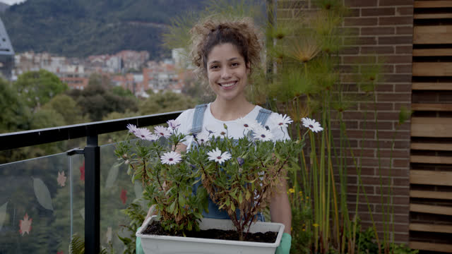 happy young woman gardening in her terrace looking at camera smiling while holding a flower pot - colombia stock videos & royalty-free footage