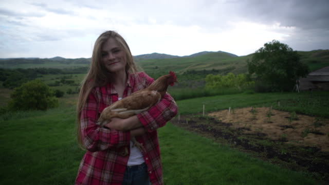 stockvideo's en b-roll-footage met ms happy young woman holding a chicken in her arms - alleen één tienermeisje