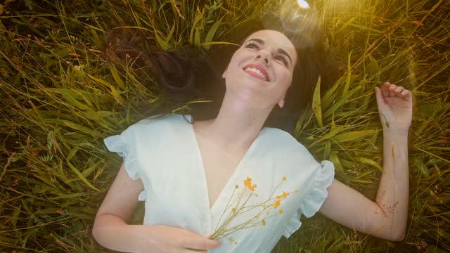 vídeos y material grabado en eventos de stock de slo mo mujer joven feliz con un vestido blanco acostado en la hierba - acostado