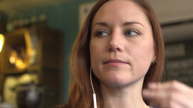 a happy young woman listening to music on her headphones - inserting stock videos & royalty-free footage