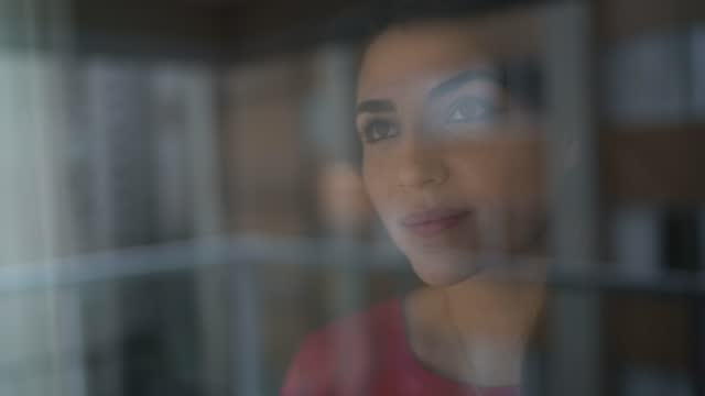 happy young woman looking through window - candid stock videos & royalty-free footage
