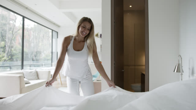 happy young woman making her bed looking cheerful - sheet stock videos & royalty-free footage