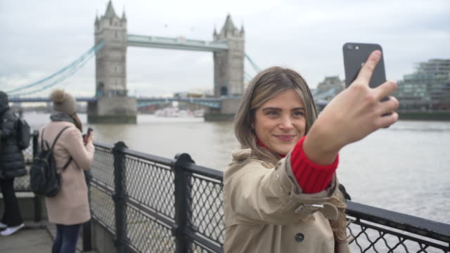 a happy young woman making selfie pictures at tower bridge, london, uk - tourist stock videos & royalty-free footage