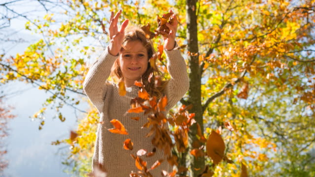 happy young woman playing with autumn leaves in park - windswept stock videos & royalty-free footage