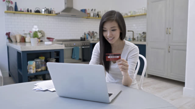 Happy young woman purchasing online through her laptop
