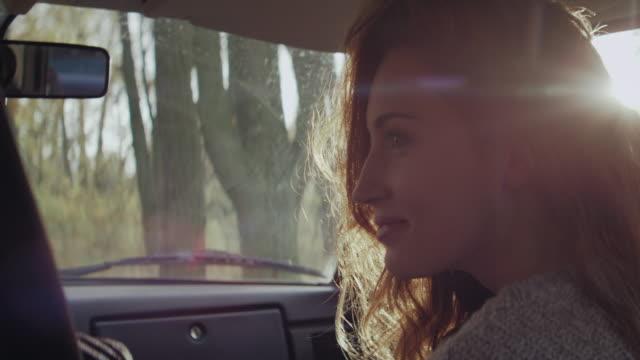 Glückliche junge Frau im Auto fahren im Wald