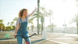Happy young woman riding the bicycle.