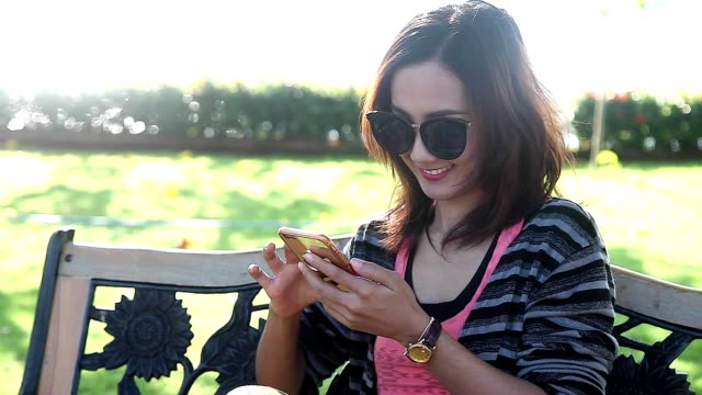 happy young woman sitting in the park and using smartphone chat to friend - sending stock videos and b-roll footage