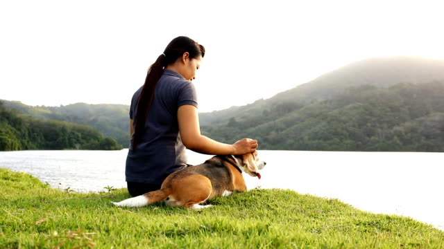 Glückliche junge Frau sitzt mit Hund auf den Fluss