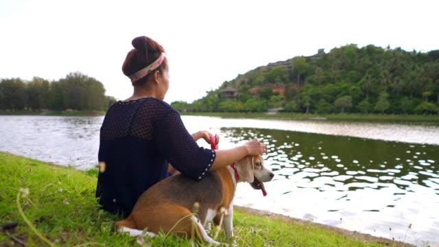lycklig ung kvinna sittande med sällskapsdjur hund i en park - korslagda ben bildbanksvideor och videomaterial från bakom kulisserna