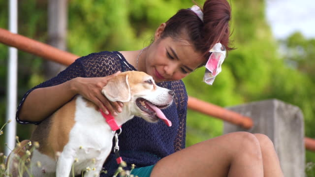 Happy young woman sitting with pet dog in a park