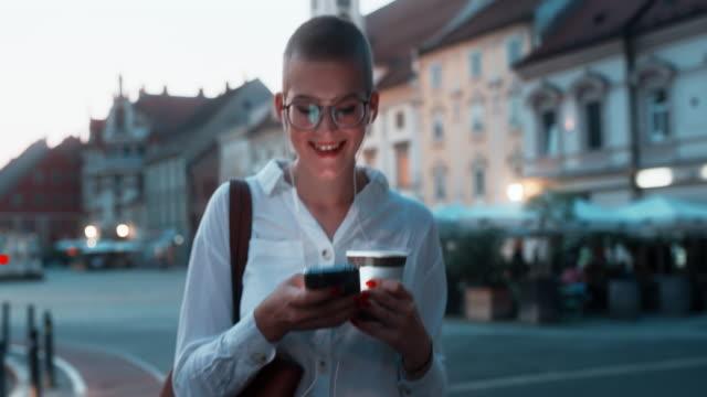 ms happy junge frau lächelnd, während mit einem smartphone in der stadt - dämmerung stock-videos und b-roll-filmmaterial