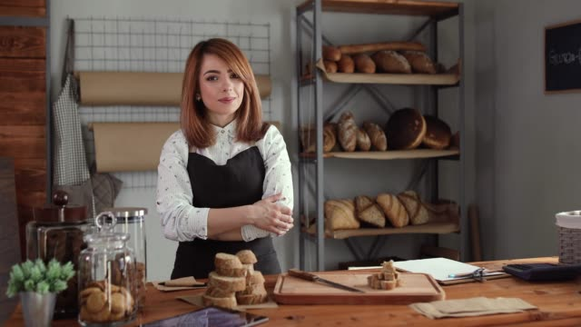 happy young woman standing confidently in her bakery - entrepreneur stock videos & royalty-free footage