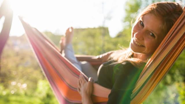 glückliche junge frau schaukeln in einer hängematte unter einem baum im hinterhof - liegen stock-videos und b-roll-filmmaterial