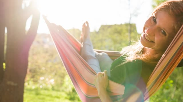 happy young woman swinging in a hammock under a tree in backyard - laziness stock videos and b-roll footage