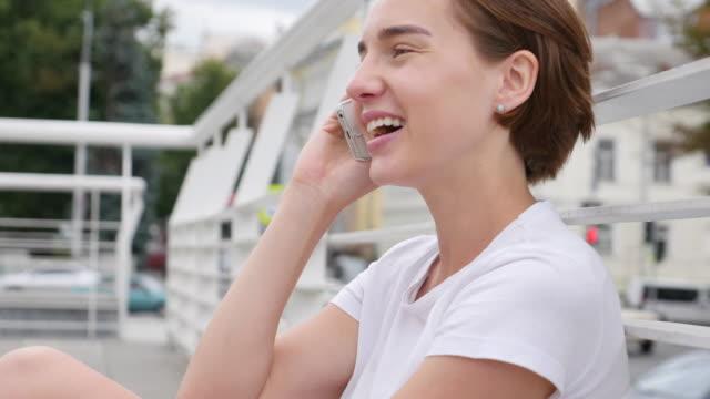 vídeos y material grabado en eventos de stock de mujer joven feliz hablando por teléfono inteligente - camiseta blanca