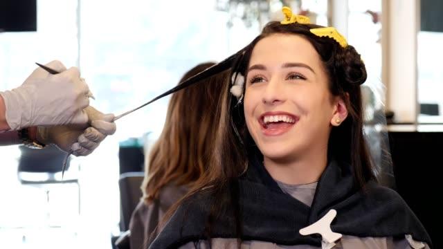 vídeos de stock, filmes e b-roll de mulher jovem feliz fala com cabeleireiro masculino como ele pinta seu cabelo - pincel