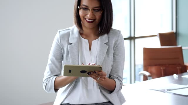 Happy young woman uses digital tablet in office