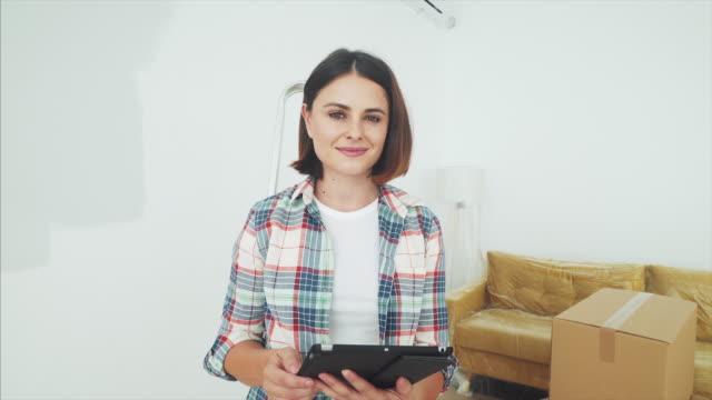 vídeos y material grabado en eventos de stock de feliz mujer joven usando una tableta en un nuevo hogar. - reforma